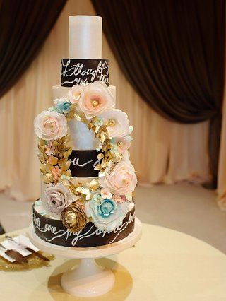 seven-layer-wedding-cake-with-song-lyrics-on-each-layer-with-pink-blue-gold-sugar-flower-gold-wreath