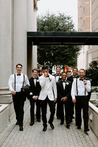 groom-in-white-tuxedo-jacket-black-bow-tie-groomsmen-in-suits-and-suspenders-bow-ties
