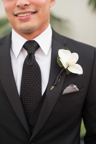 man-in-black-and-white-tie-with-single-flower-on-lapel