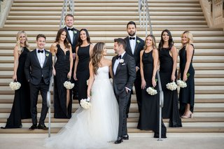 bride and groom with bridesmaids in black dresses and groomsmen in tuxedos velvet bow ties