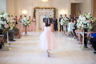 back-of-flower-girl-walking-down-aisle-with-ribbon-in-hair-and-ribbons-on-pink-shoes
