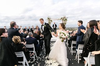 wedding-guests-standing-and-clapping-high-five-couple-after-rooftop-wedding-ceremony-view-of-city