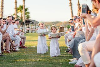 flower-girls-with-wide-baskets-in-long-white-dresses-and-flower-crowns-guests-take-pictures