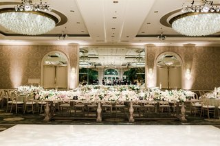 wedding reception long wood table low centerpiece pink white flowers greenery crystal chandelier