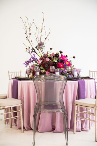 wedding-reception-single-chair-with-grey-ghost-chair-purple-pink-centerpiece-branches