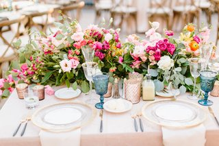 wedding-reception-sweetheart-table-gold-charger-plate-pink-and-orange-flowers-greenery-blue-goblets