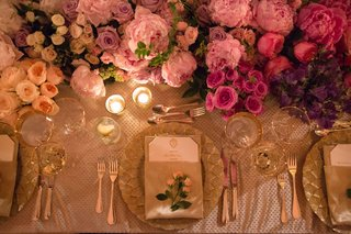 wedding-reception-place-setting-with-rosebuds-and-pink-white-purple-flowers-at-long-table