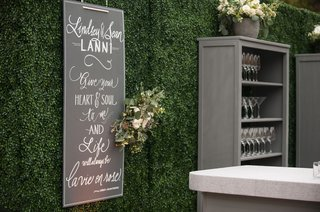 outdoor-wedding-green-boxwood-hedge-wall-chalkboard-sign-louis-armstrong-quote-grey-bookshelf-bar