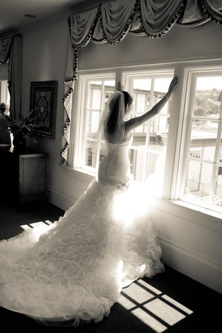 black-and-white-photo-of-bride-in-a-fitted-maggie-sottero-gown-with-ruffled-skirt-and-train