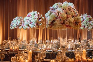 wedding-reception-with-tall-flower-arrangements-glass-crystal-vases-gold-linens-candles-drapery