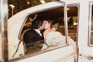 groom-kissing-bride-in-getaway-car-after-wedding-grand-exit-bridal-gown-bouquet
