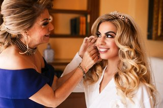 bride-in-white-robe-glamorous-curls-tiara-veil-mother-of-bride-helping-with-earrings-blue-gown