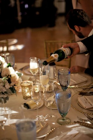 wedding-reception-server-pouring-champagne-sparkling-wine-into-glass-of-wedding-guest