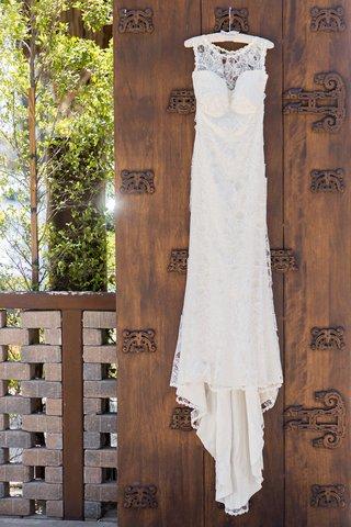 claire-pettibone-wedding-dress-on-white-hanger-before-wedding-ceremony-wood-door-at-venue