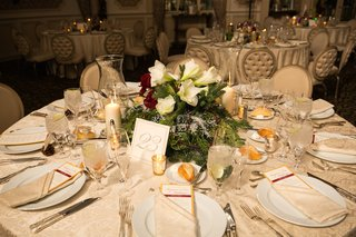 holiday-wedding-reception-table-with-evergreen-white-amaryllis-red-roses-holly-christmas-lights