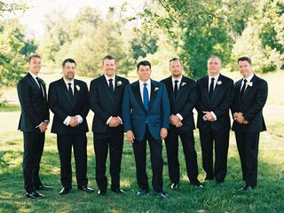 groom-in-navy-tuxedo-jacket-with-black-lapels-and-blue-tie-with-groomsmen-in-dark-suits