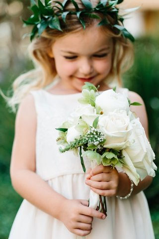 flower-girl-in-white-dress-with-green-flower-crown-holding-white-rose-bouquet-of-flowers