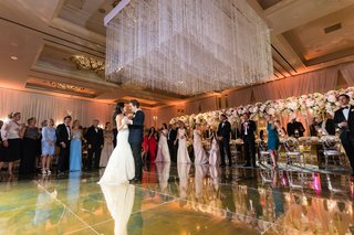 bride-in-monique-lhuillier-wedding-dress-on-dance-floor-gold-with-crystal-ceiling-installation-over