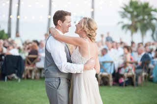 bride-in-a-love-marley-dress-with-lace-bodice-tulle-skirt-dances-with-groom-in-grey-vest-pants