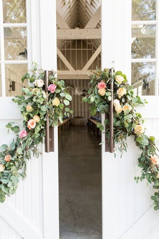 large-white-barn-farmhouse-doors-decorated-with-greenery-pink-rose-yellow-rose-orange-rose-flowers