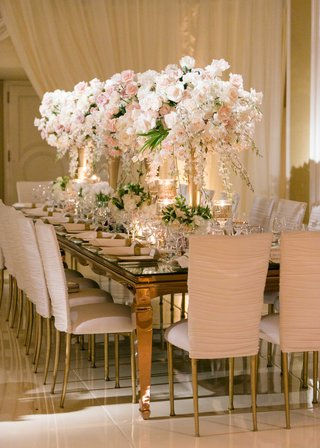 mirror-top-wedding-reception-table-with-white-chameleon-chairs-ruched-and-white-pink-centerpieces