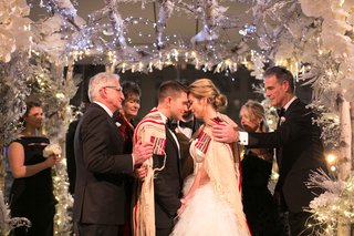 jewish-wedding-with-bride-and-groom-under-chuppah-tallit-fathers-winter-lights-flowers-white-silver