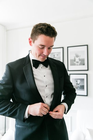 groom-in-grooms-suite-black-and-white-tuxedo-buttoning-up-before-wedding