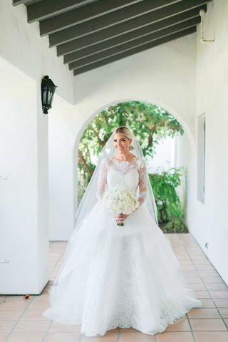 bride-in-long-sleeve-lace-carolina-herrera-ball-gown-with-veil-and-ivory-bouquet