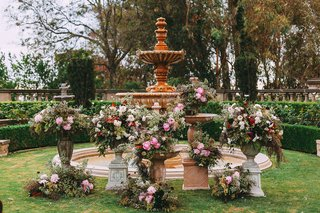 wedding-ceremony-outdoors-fountain-at-altar-pink-flowers-in-vintage-antique-style-vases-urns
