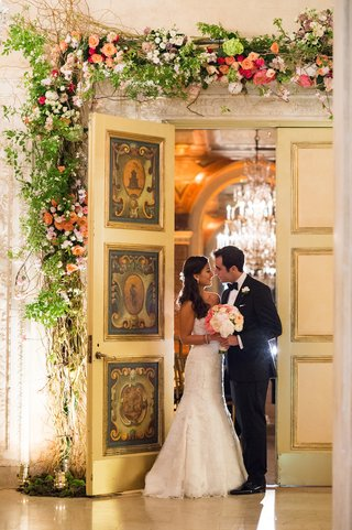 bride-and-groom-under-floral-door-at-the-plaza-hotel