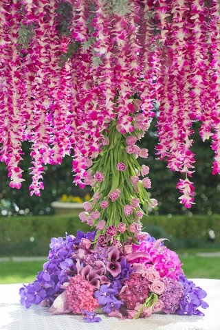 wedding-reception-table-with-hot-pink-orchid-garlands-trunk-of-pink-tulips-purple-orchids-roses