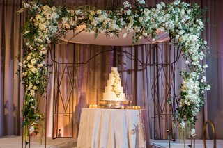 white-cake-with-white-flowers-under-canopy-of-white-flowers-and-leaves
