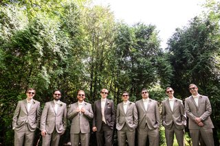 a-groom-and-groomsmen-in-gray-tuxedos-with-pink-accents-posing-outside-with-sunglasses