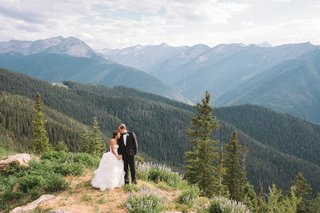 bride-and-groom-standing-on-mountain-among-trees
