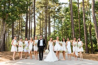 bridesmaids-in-mismatched-white-dresses-short-with-bridesman-in-tuxedo-in-woods-georgia