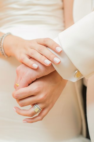 bride-in-neutral-manicure-nails-with-yellow-diamond-engagement-ring-and-grooms-yellow-gold-band