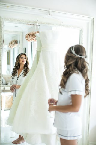bride-in-short-summer-pajamas-long-hair-headpiece-crown-looking-in-mirror-at-wedding-dress-vera-wang