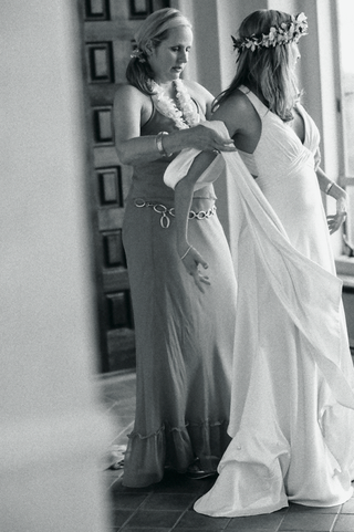 black-and-white-photo-of-woman-helping-bride-get-dressed