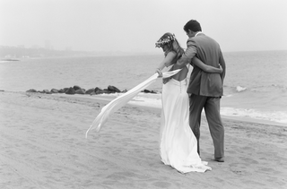 black-and-white-photo-of-bride-and-groom-walking-on-beach