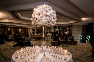wedding guests in room outside of ballroom with escort card table pink white roses silver cards