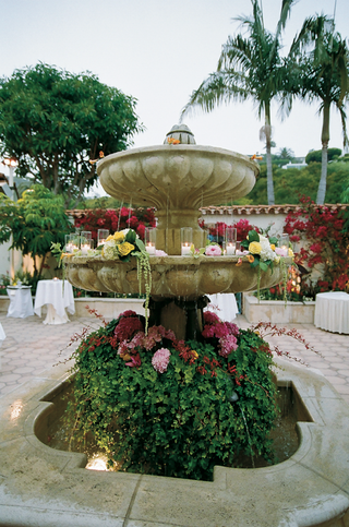 stone-fountain-covered-with-greenery-flowers-and-candles