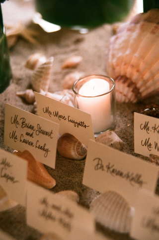 candlelit-place-cards-on-top-of-sea-shells