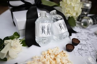 wedding welcome bag custom water bottles with monogram chocolate popcorn map and can wine