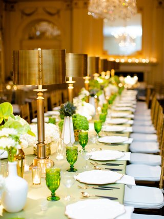wedding reception green linen and glassware goblet gold brass table lamp decor