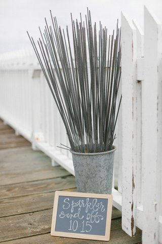 diy-chalkboard-sign-for-sparkler-send-off-with-tall-sparklers-in-tin-next-to-white-picket-fence