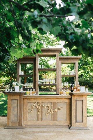 jillian-murray-and-dean-geyer-outdoor-wedding-reception-wood-bar-gold-calligraphy-sign-names-shelves