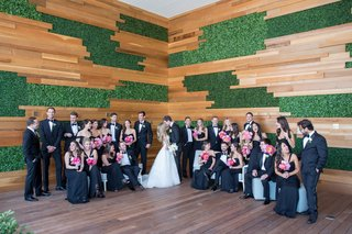 wedding-party-in-black-tie-attire-tuxedo-bow-tie-wood-greenery-wall-decor
