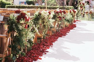 white-aisle-runner-with-red-rose-petals-and-flowers-on-wooden-chairs