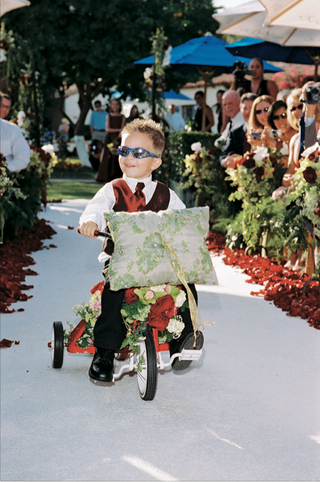 young-boy-wearing-red-vest-on-flower-embellished-red-tricycle