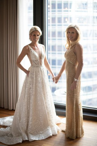 bride in berta wedding dress with pockets and sparkle embroidery holding hands with mom in gold sequin dress
